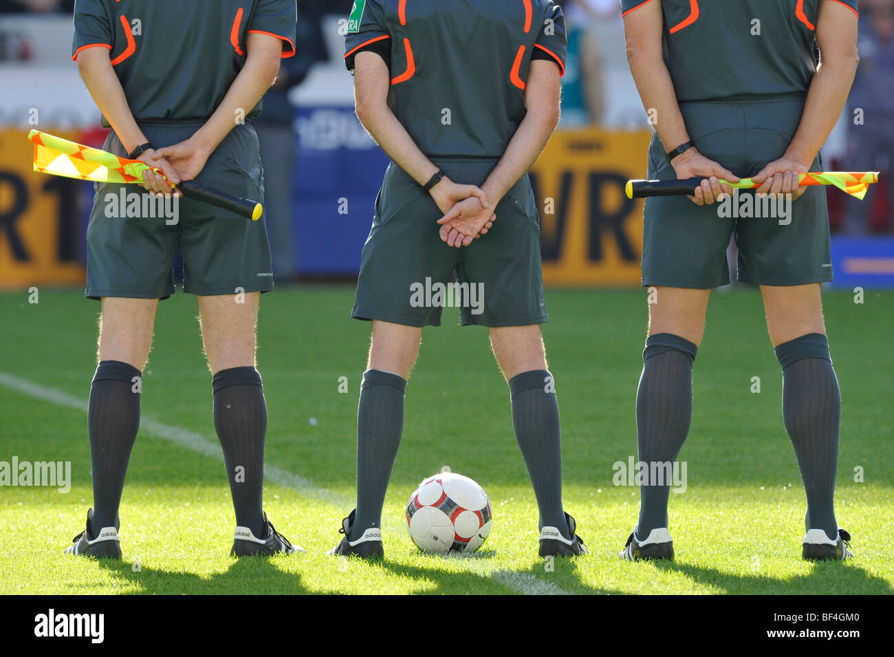 Referee and two linesmen, ball, flag during a minute's silence in the stadium, Mercedes-Benz Arena stadium, - Stock Image