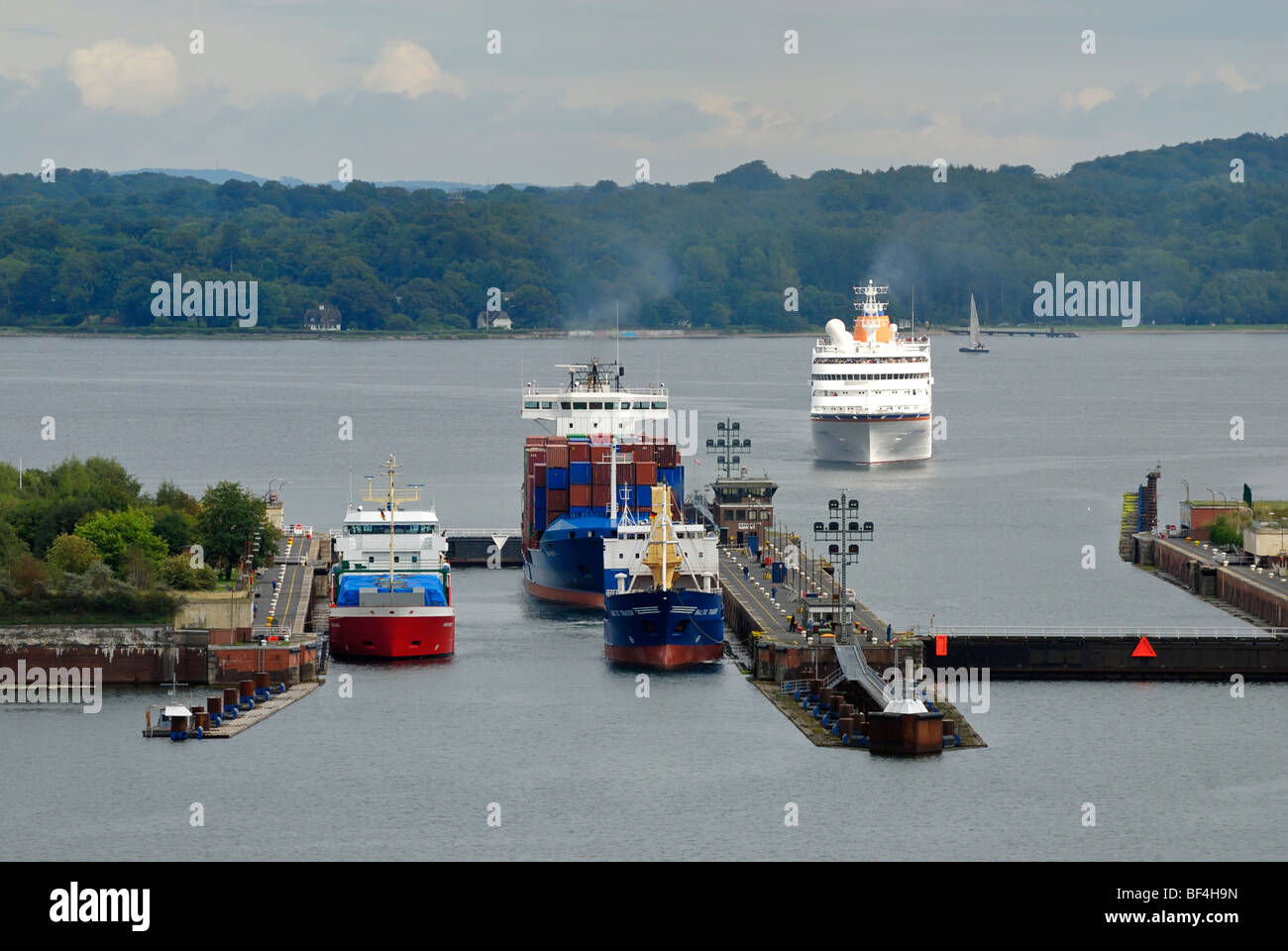 Shipping traffic at the Schleuse Holtenau lock, container ships and cruise ship, Kiel, Schleswig-Holstein, Germany, - Stock Image