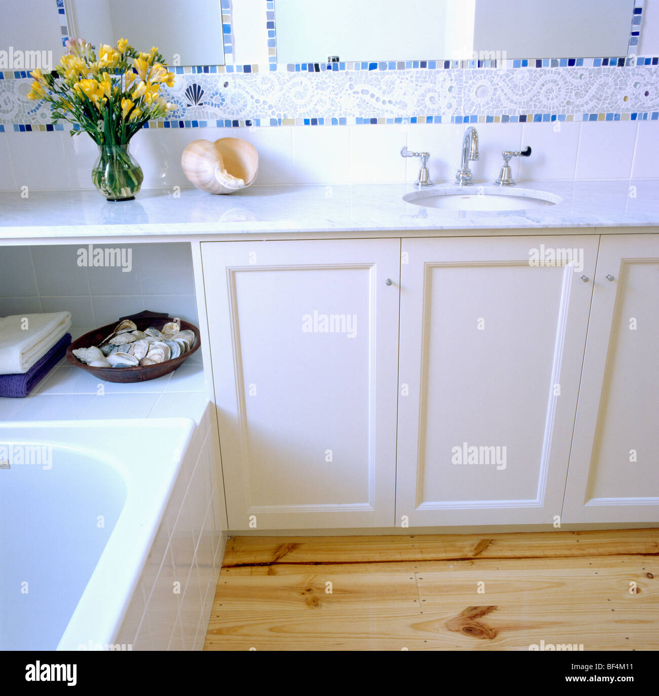 Mosaic tiled border above fitted vanity unit in modern white bathroom - Stock Image