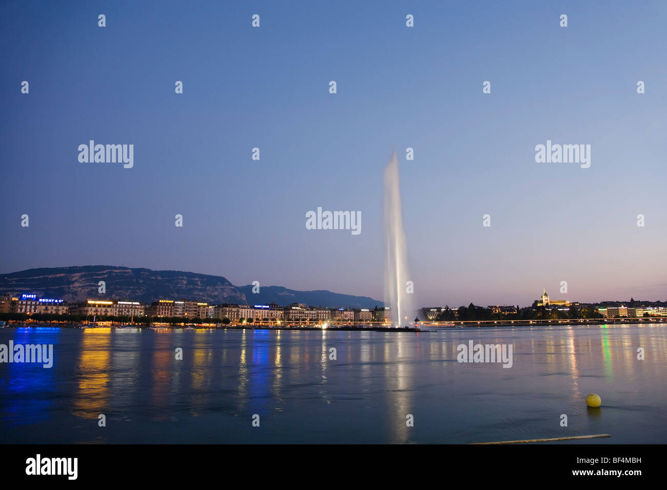 Illuminated Jet d'Eau (one of the largest fountains in the world) and St. Pierre Cathedral at night, Lake Geneva, - Stock Image