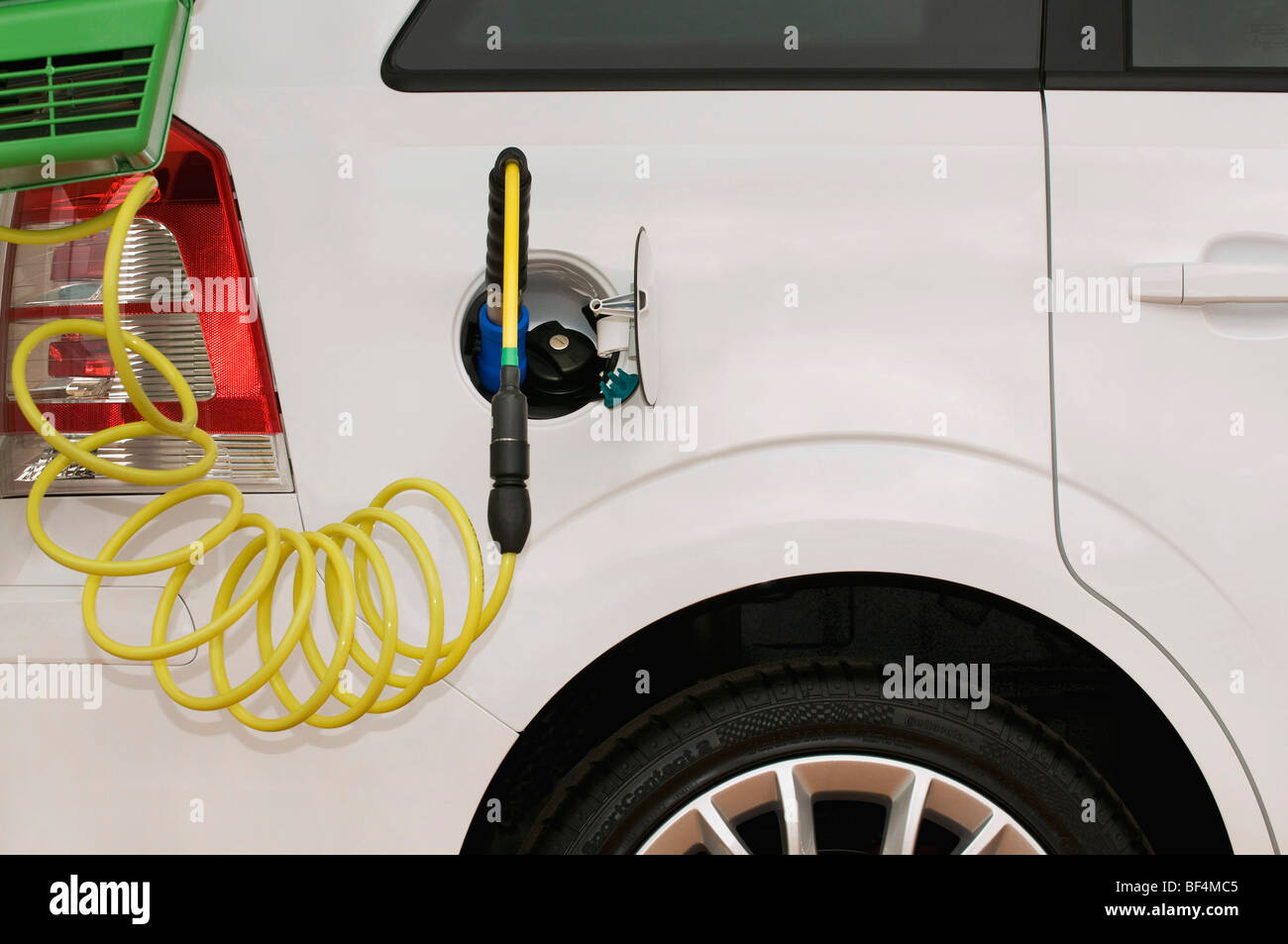 Refueling a car with a gas nozzle next to a conventional petrol cap - Stock Image