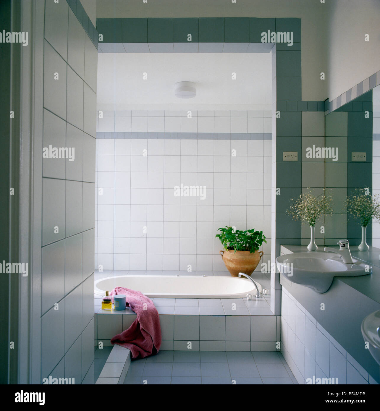 Modern white bathroom with pink towel on low bath with white tiled ...