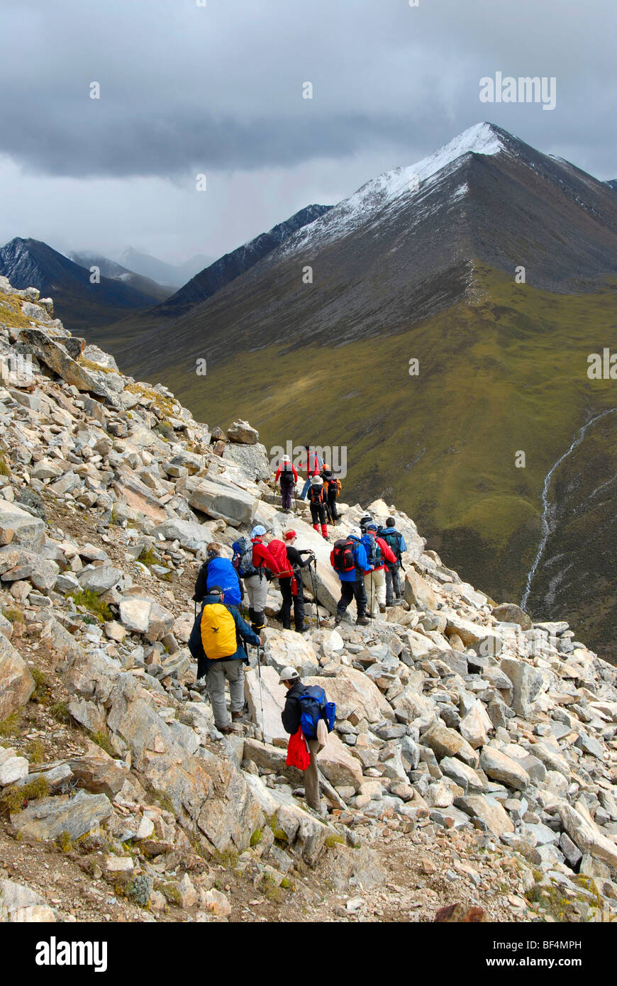 Trekking tourism, group of hikers, stony path, Shug-La Pass 5250 m, an old pilgrims' path through the high mountains - Stock Image