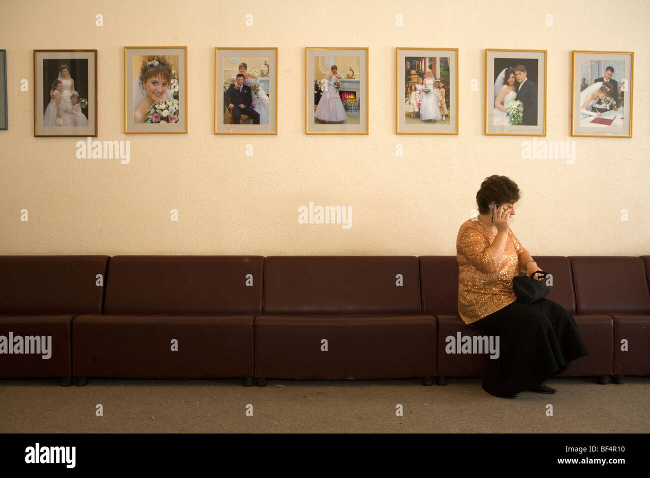 Wedding guest in waiting room with wedding photographs on wall Stock ...