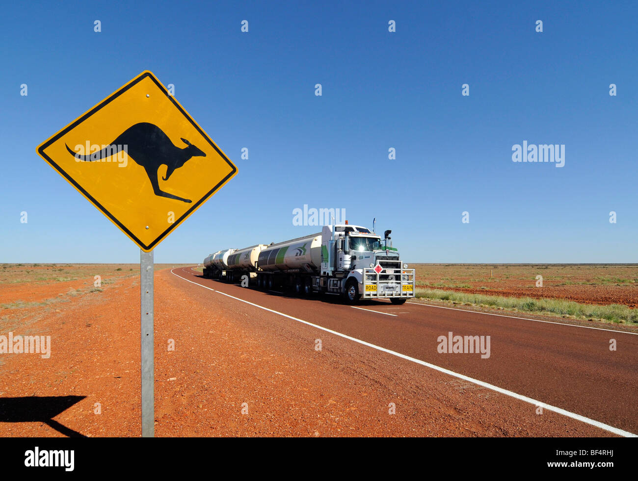 A road train passing by a kangaroo road sign in the Australian outback. - Stock Image