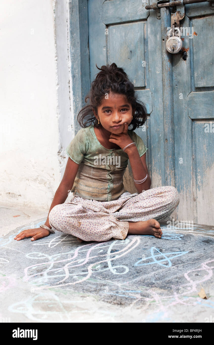 Young Indian street girl sitting by a door in an Indian street - Stock Image