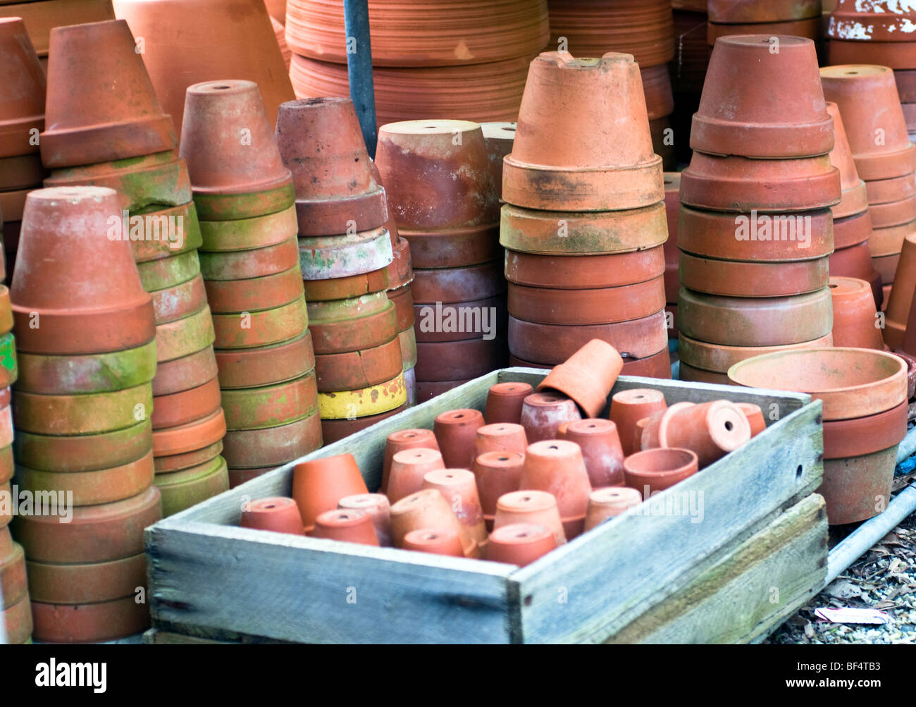 Terracotta flower pots without plants stacked in rows. - Stock Image