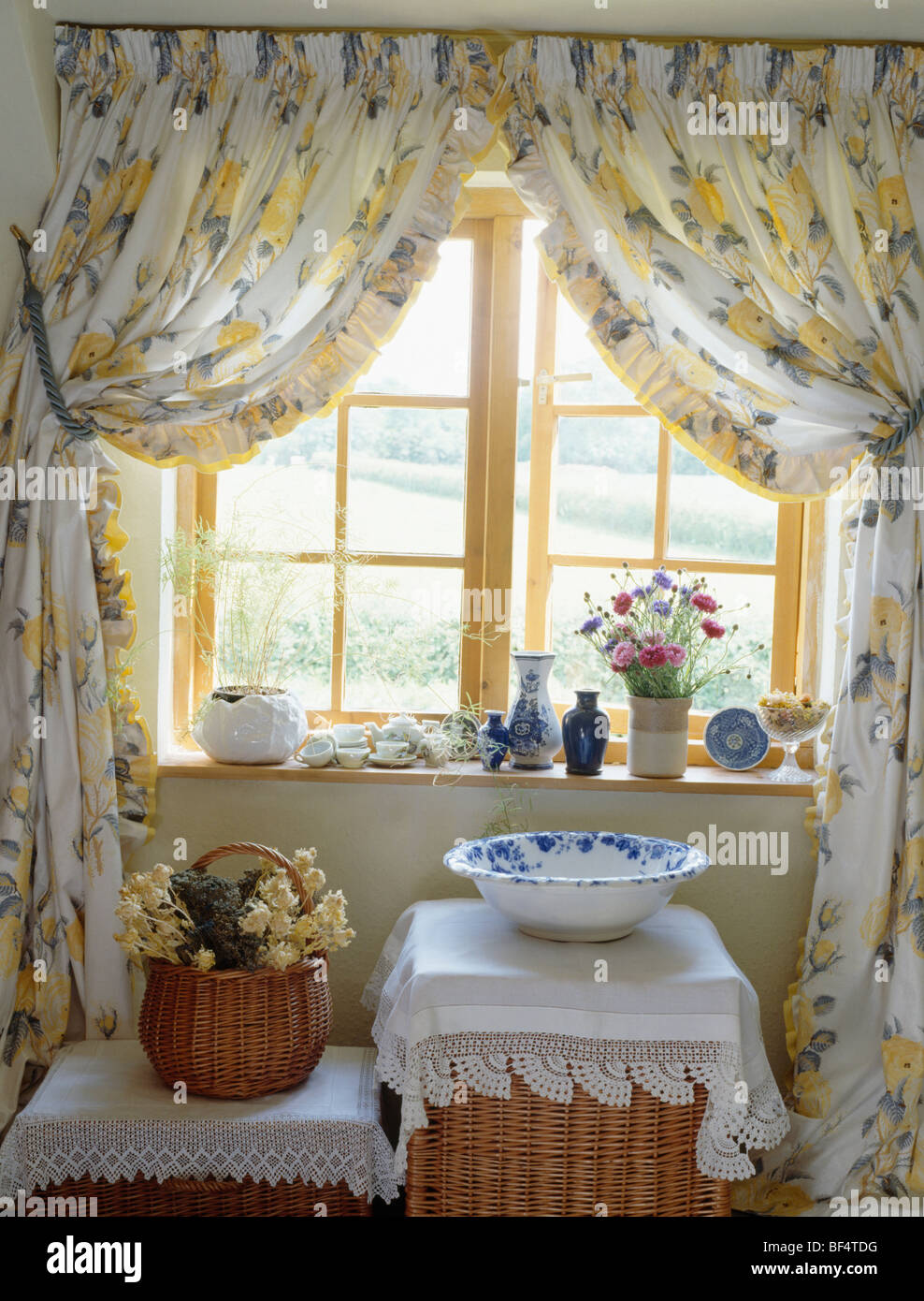 Floral Curtains On Open Casement Window In Cottage Bathroom With Pottery Bowl And Lace Cloth Tall Basket