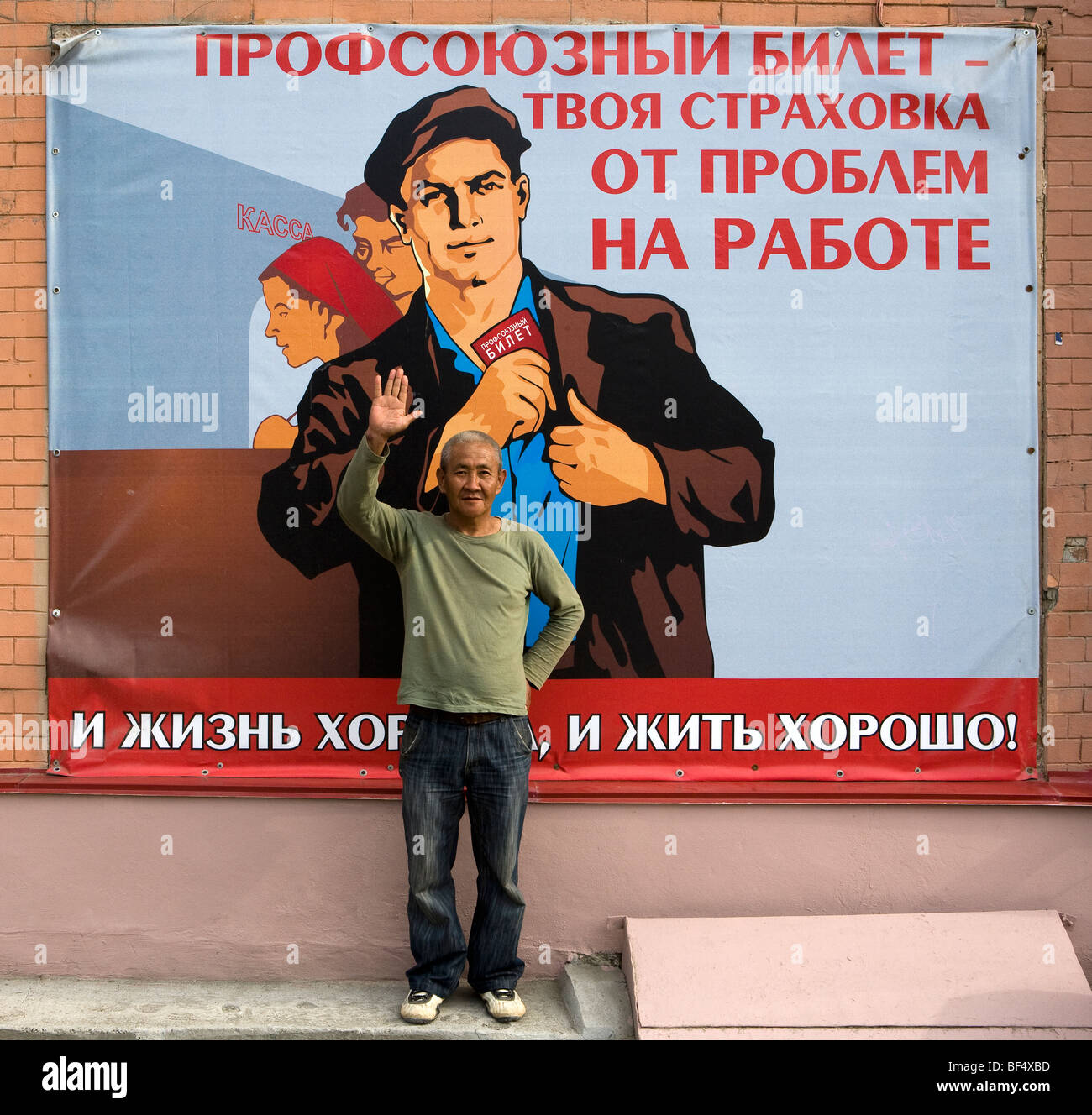 Man standing in front of traditional soviet propaganda poster, portrait, Ekaterinburg, Urals, Russia - Stock Image