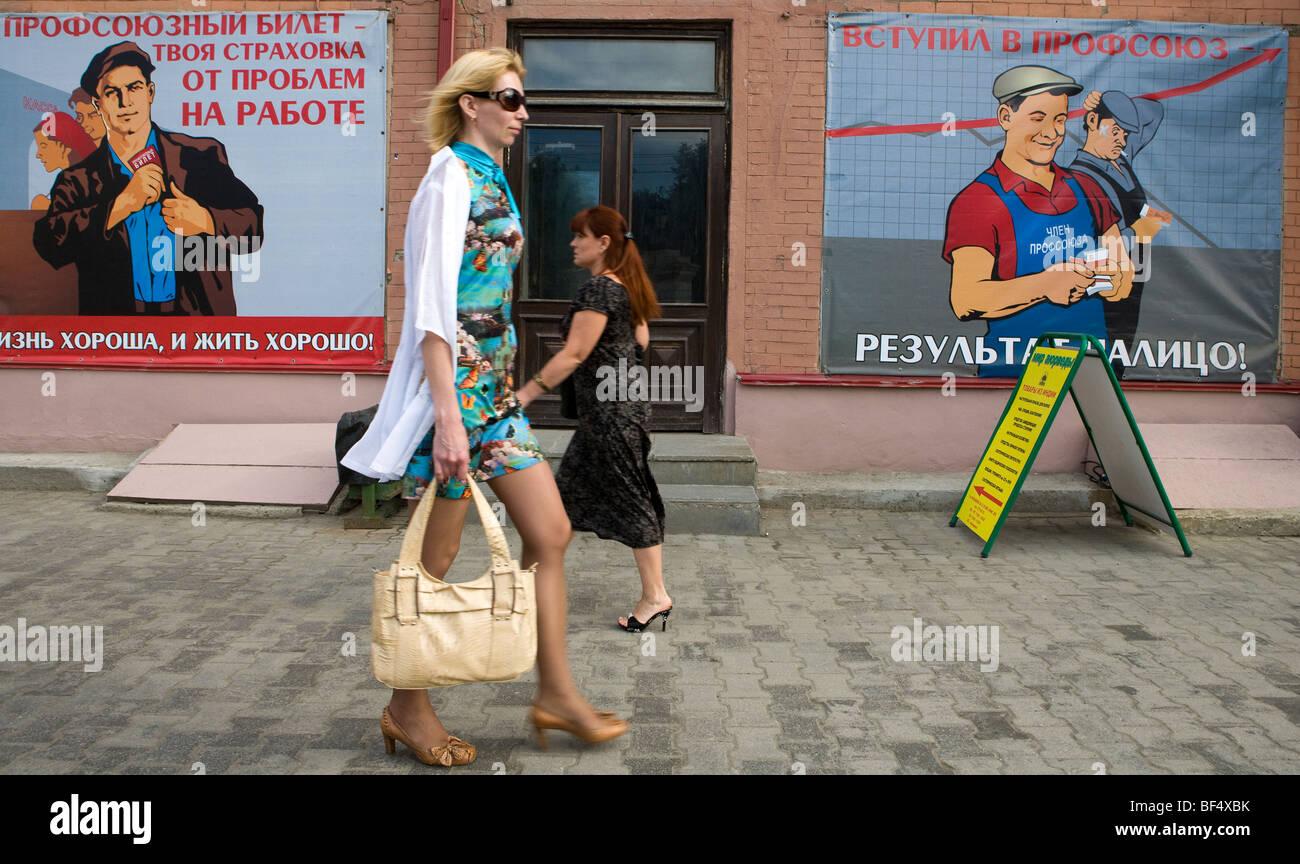 Pedestrians passing Soviet Union propaganda posters, Ekaterinburg, Urals, Russia - Stock Image
