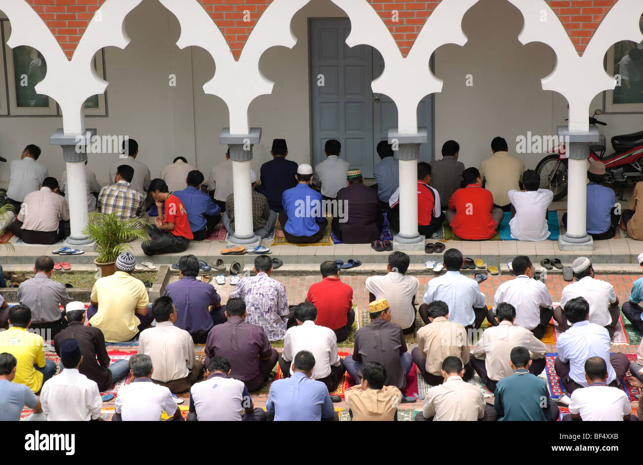 Large group of male islamic worshipers at Friday prayers in a mosque - Stock Image