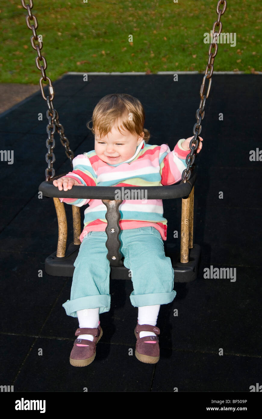 Vertical close up portrait of a little girl smiling and having great fun sitting on a swing at the park. Stock Photo