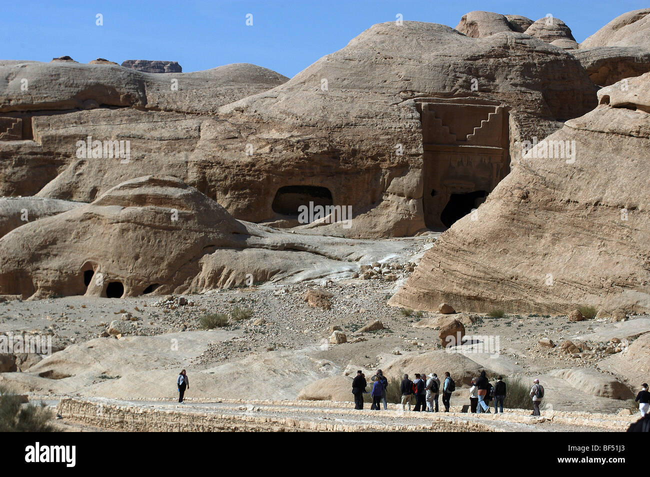 Tourists on the way to the entrance to Petra, southern Jordan admire some of the tombs. Stock Photo
