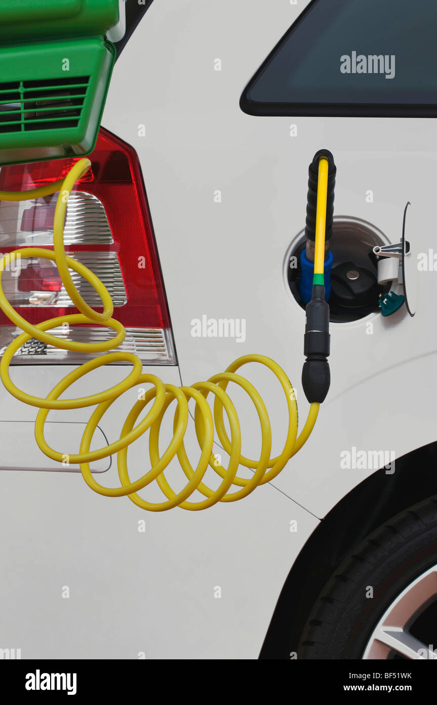 Fueling a passenger car with gas, gas pump nozzle in addition to a conventional fuel tank cap - Stock Image