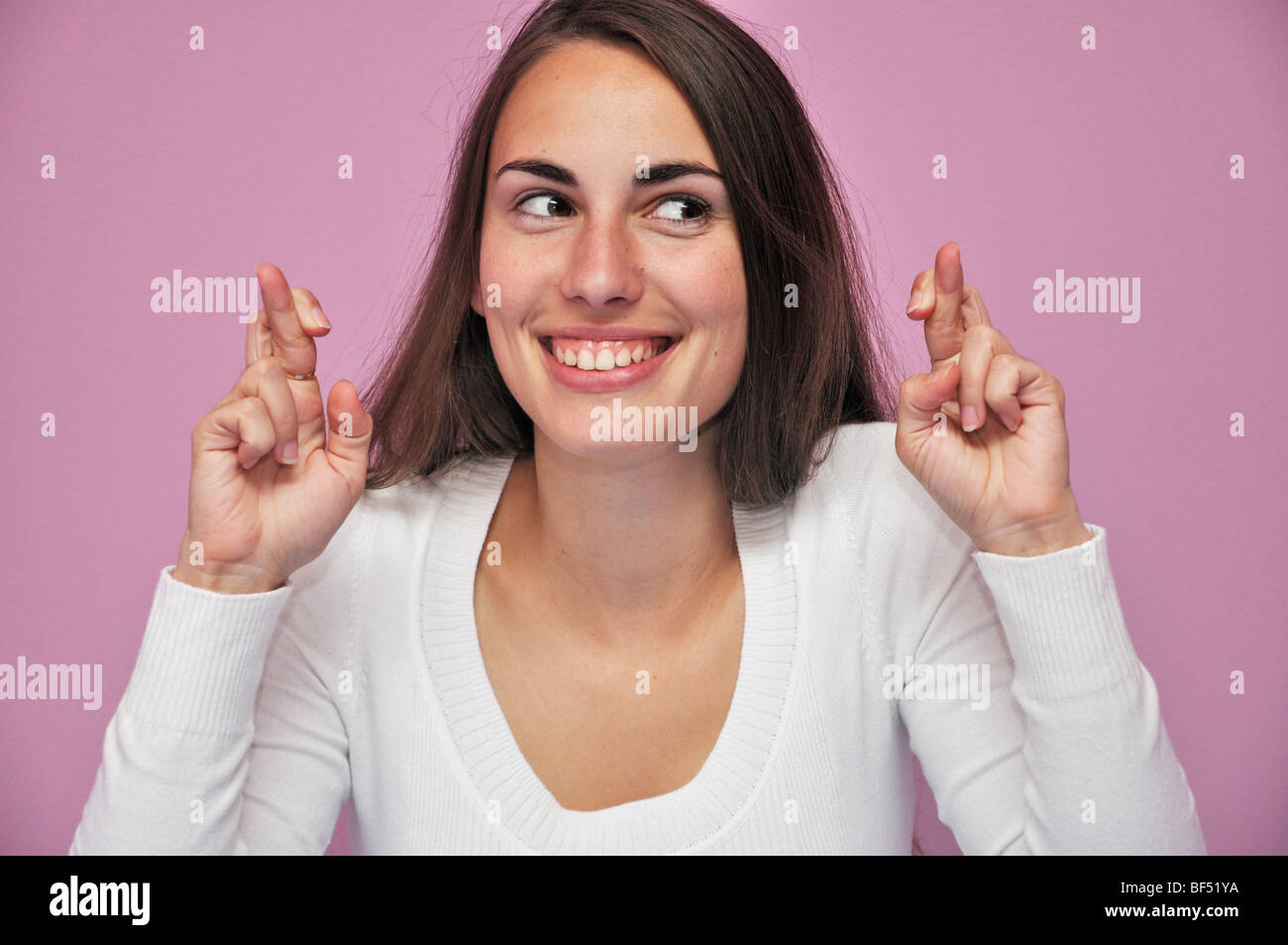 Young woman with fingers crossed - Stock Image