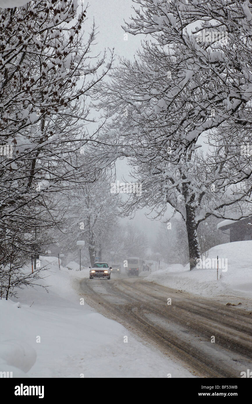 Heavy snow fall, cars with lights on driving carefully on a road, Reit im Winkl, Bavaria, Germany, Europe - Stock Image