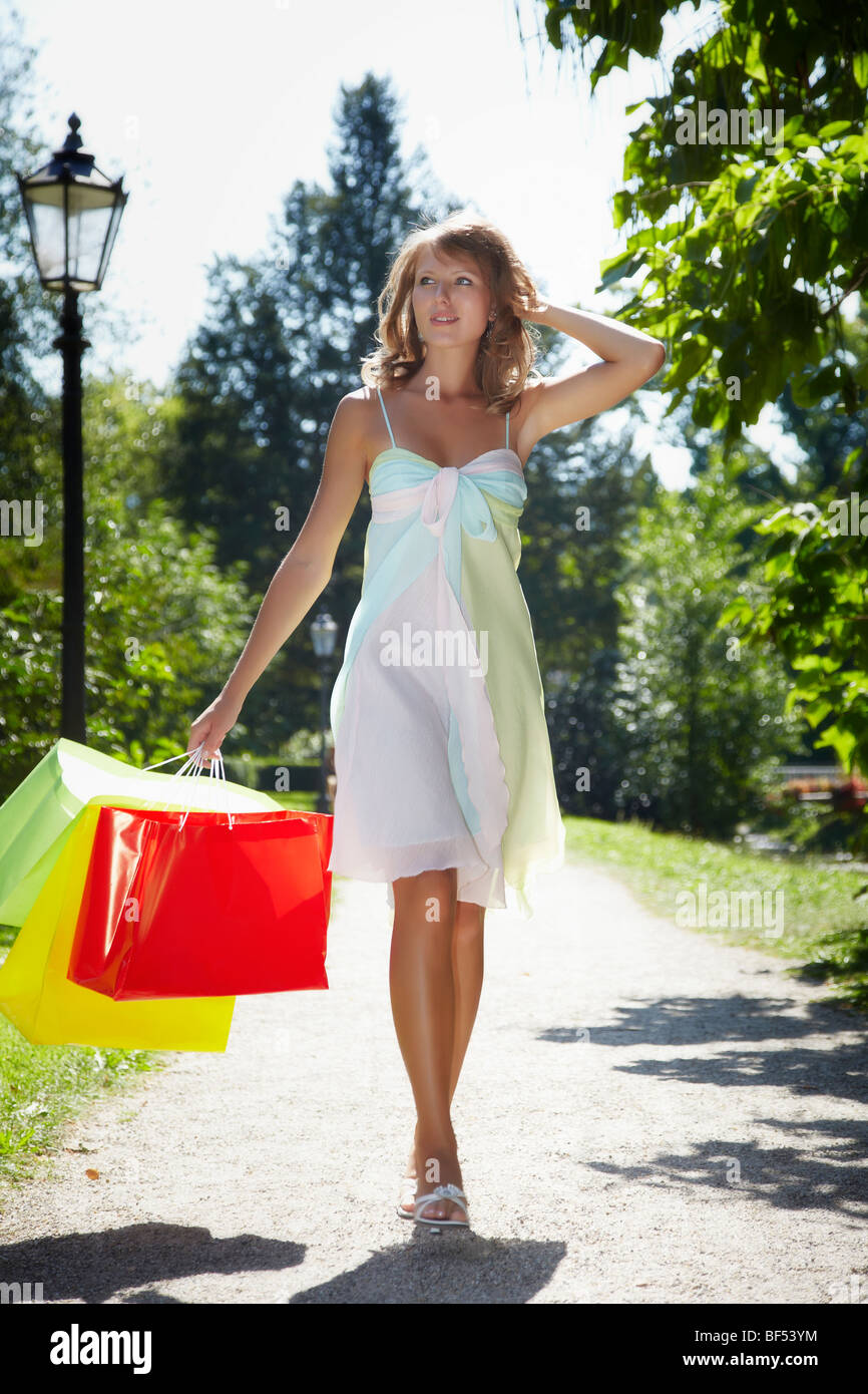 Young woman wearing a summer dress, holding shopping bags while running happily through a park - Stock Image