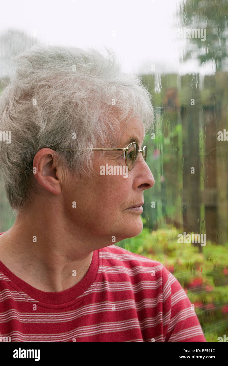 Senior woman with a despondent expression looking out through a window on a rainy day. UK Britain - Stock Image