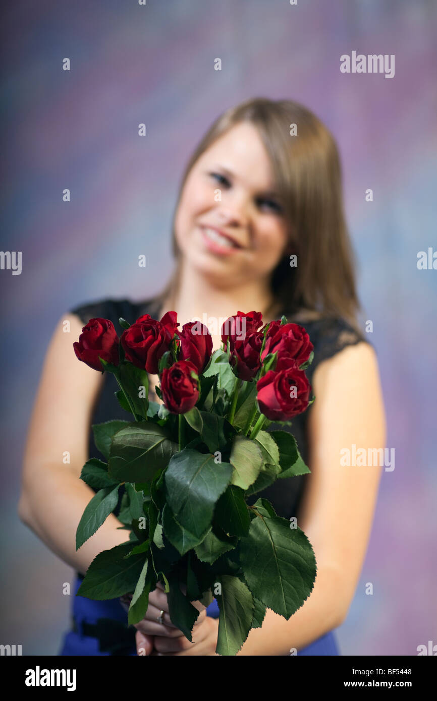 Studio, UK, Britain. Portrait of a young woman smiling and holding a bunch of red roses Stock Photo