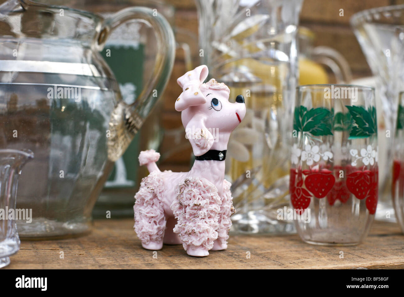 kitsch glass figurine sprightly pink poodle with gold accents displayed for sale at Hells Kitchen flea market in - Stock Image