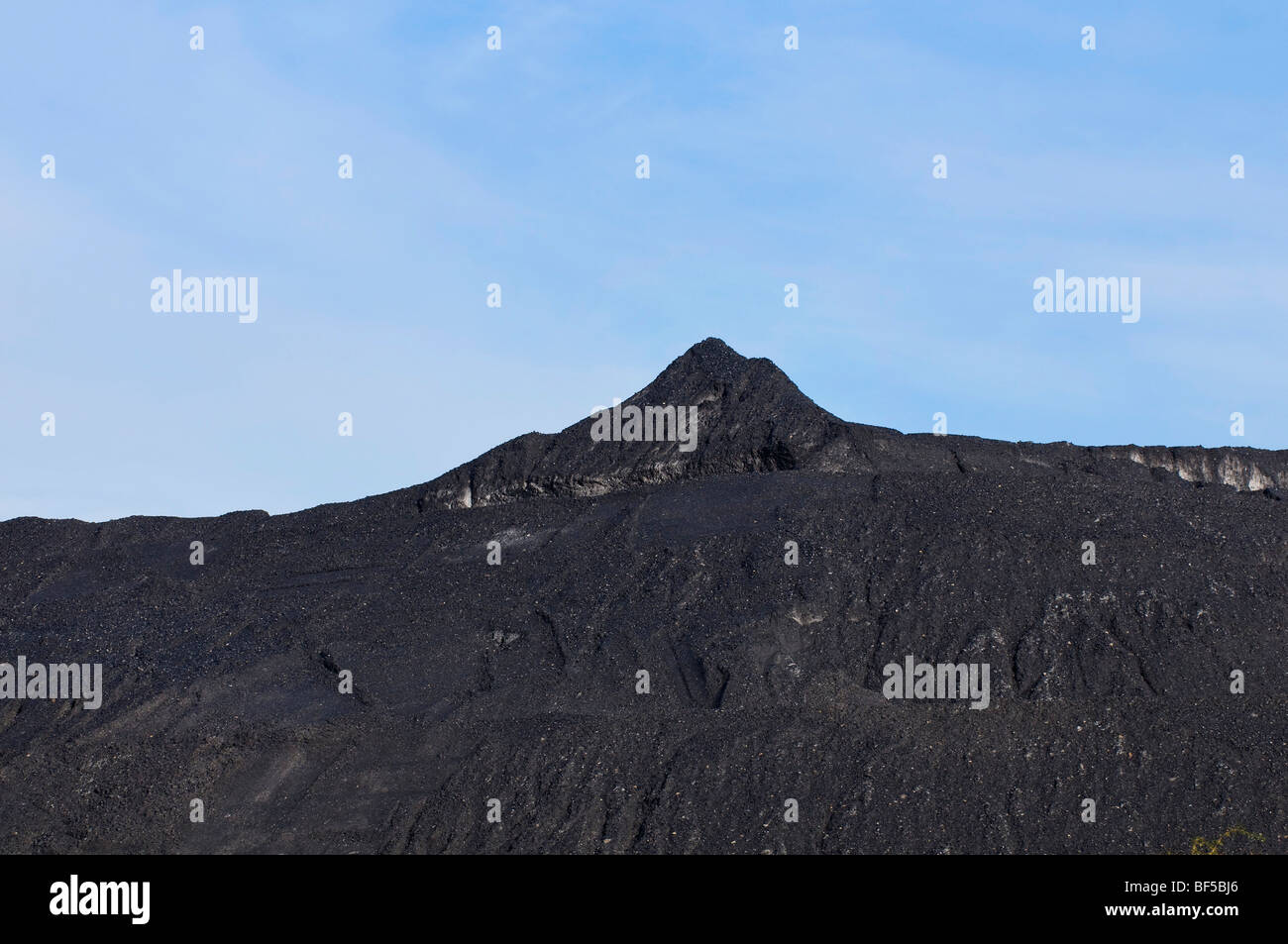 Mountain of coal against a blue sky - Stock Image