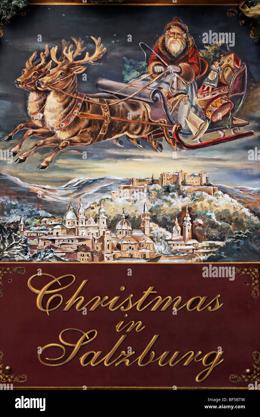 Santa Claus driving a sleigh in the sky over Salzburg, painted sign advertising a shop for Christmas decorations, - Stock Image