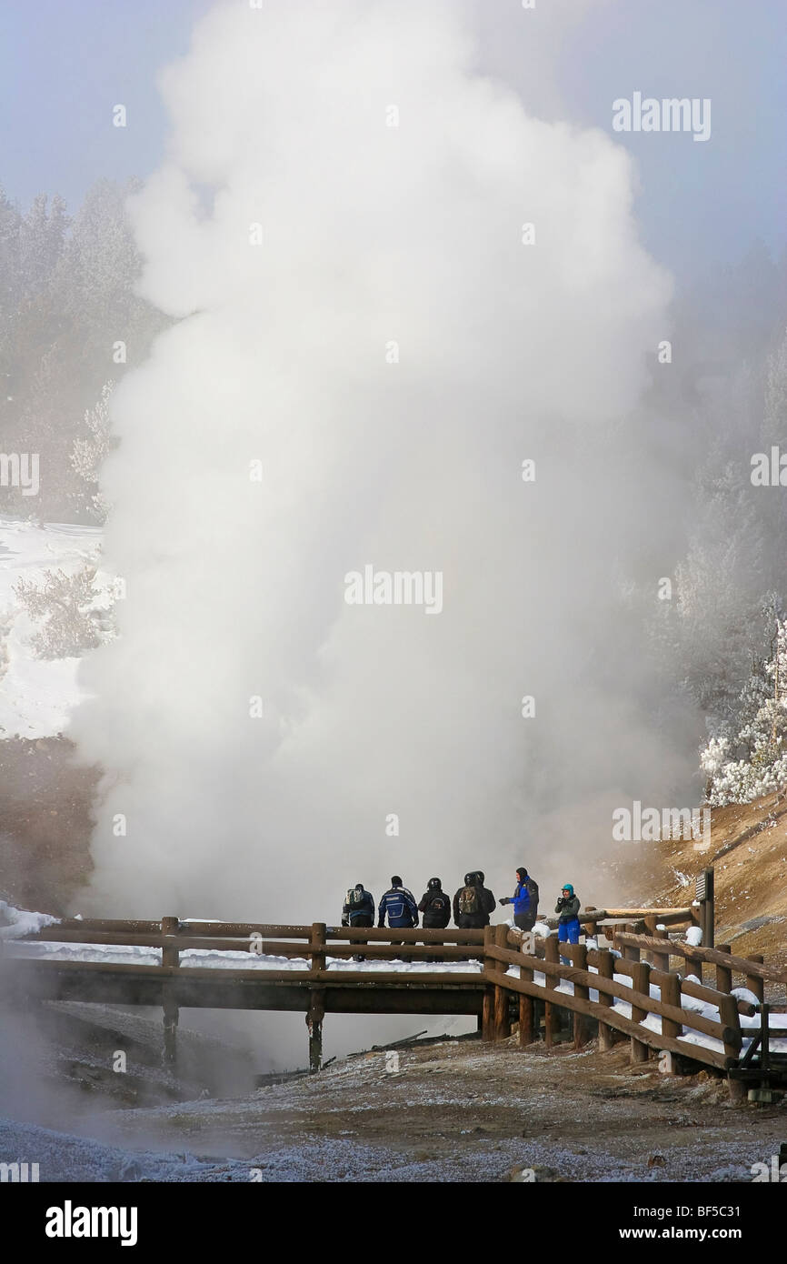 Visitors watch geyser eruption at Mud Volcano, winter, Yellowstone NP - Stock Image