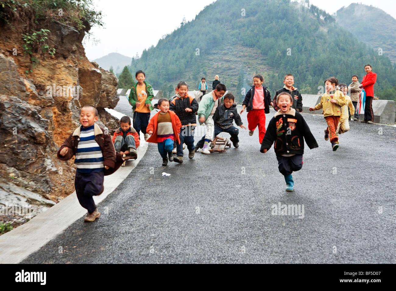 School children running on paved road, Guizhou Province, China - Stock Image