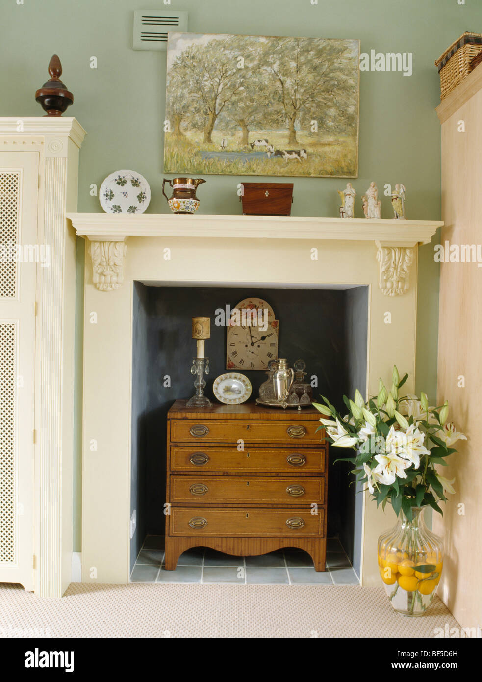 Close Up Of Small Chest Of Drawers In White Fireplace In Pale Green Cottage Dining  Room
