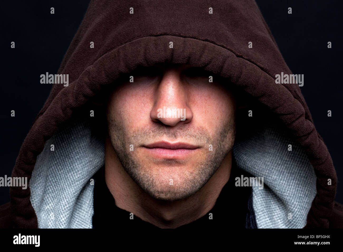 An evil looking man wearing a hooded top with his eyes hidden against a black background. - Stock Image