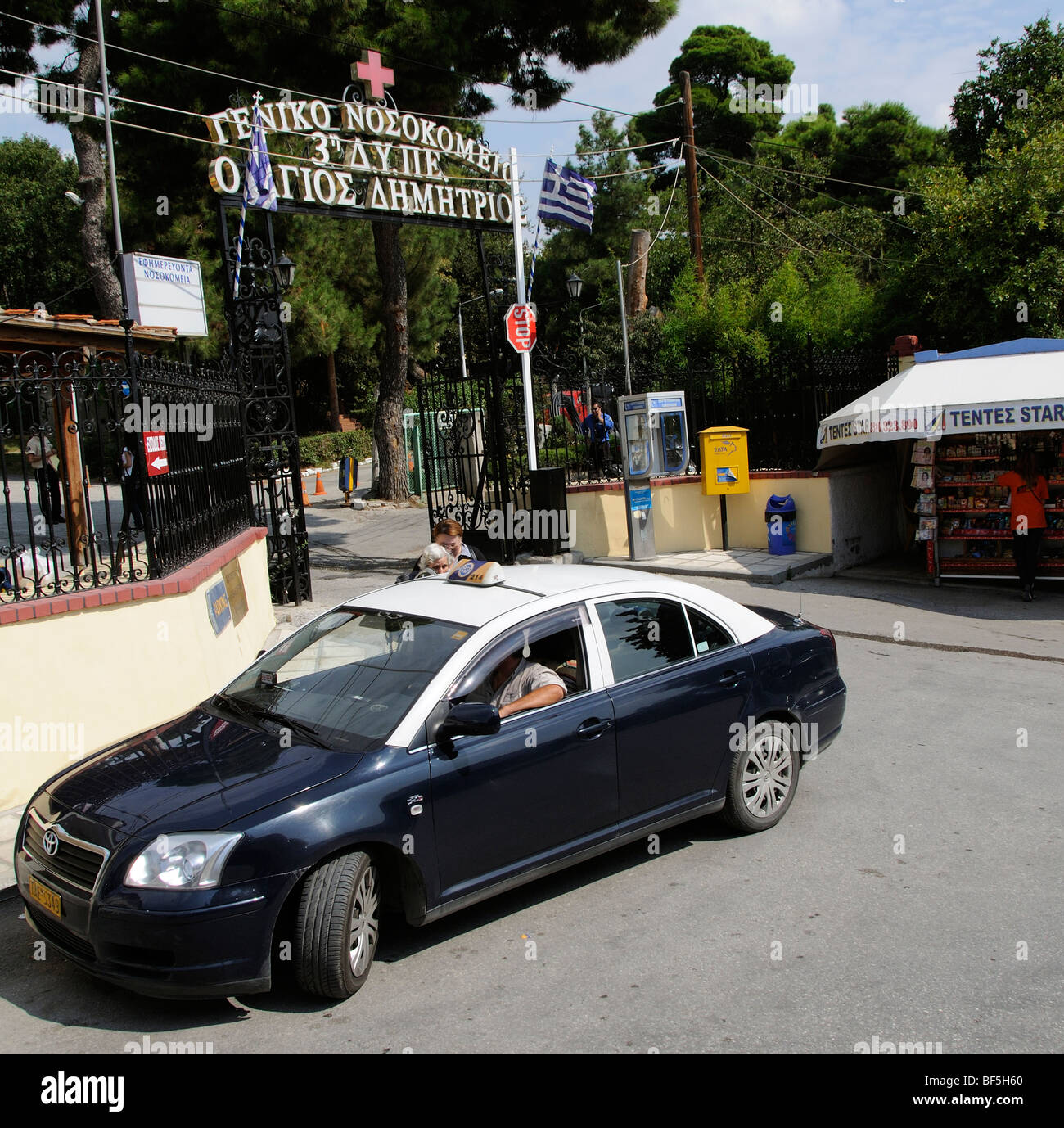 taxi picking up a fare out side the main gate of Agios Dimitrios General Hospital in Thessaloniki Greece - Stock Image