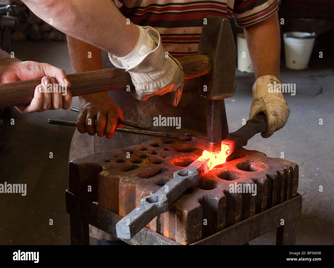 Blacksmith and his assistant at work, Berlin, Germany - Stock Image