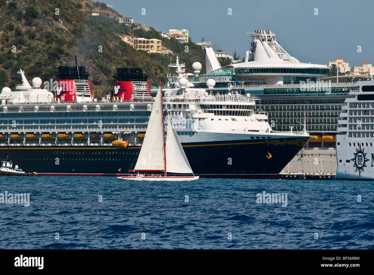 The Twelve Meter yacht CANADA sails past cruise ships in Great Bay, Philipsburg, Sint Maarten - Stock Image