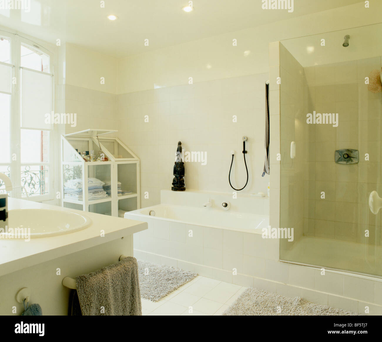 Cream townhouse bathroom with tiled wall separating bath from shower ...