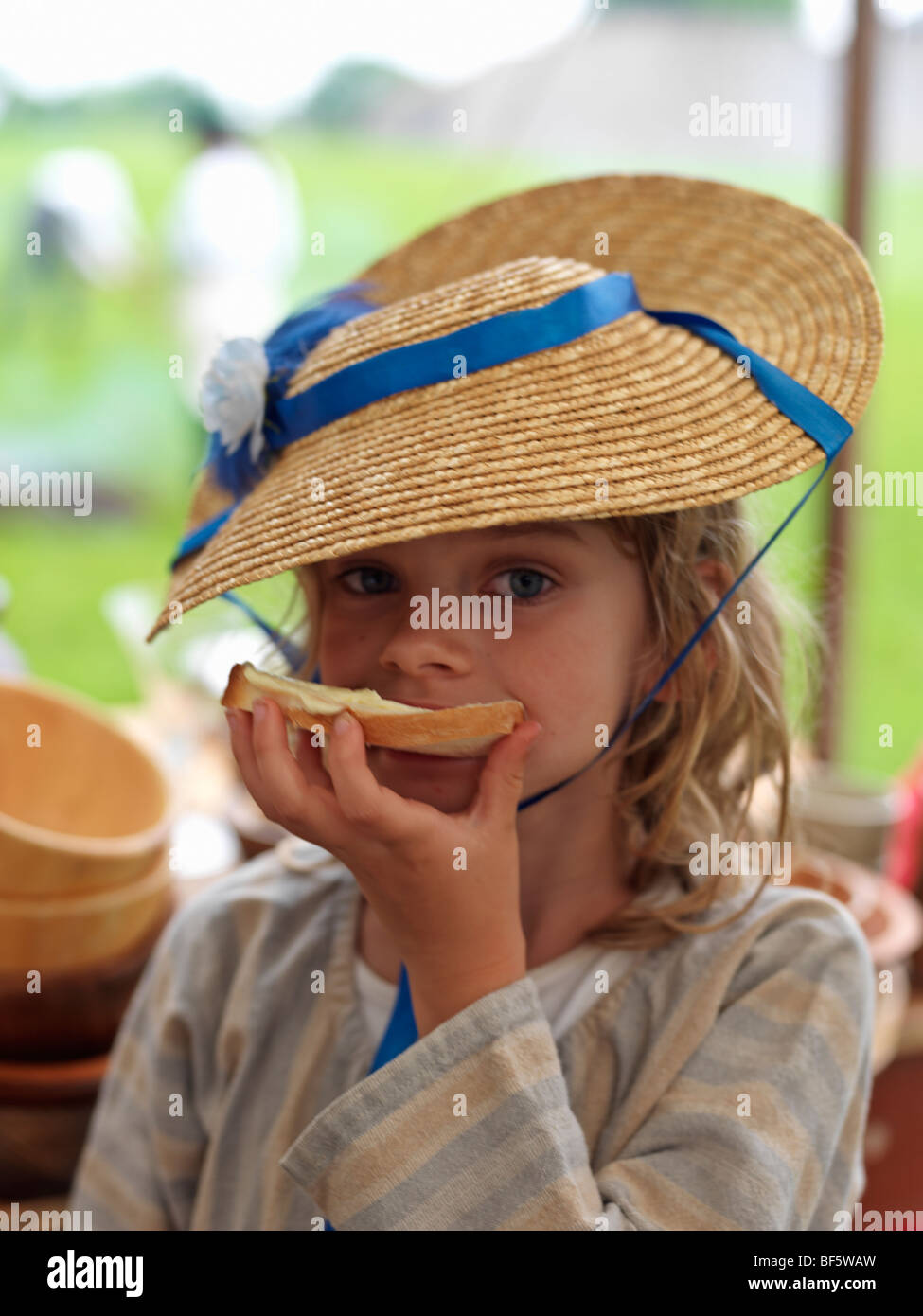 Canada, Ontario, Fort Erie, Old Fort Erie, War of 1812 reenactor in period costume. young girl eating buttered bread - Stock Image