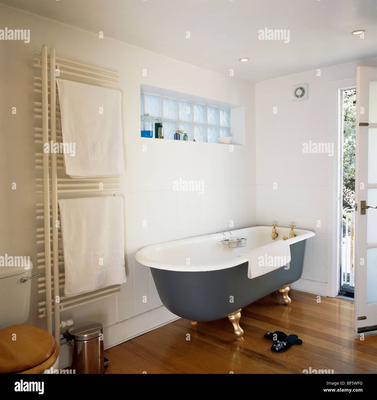 Black roll-top bath and wooden flooring in modern white bathroom ...