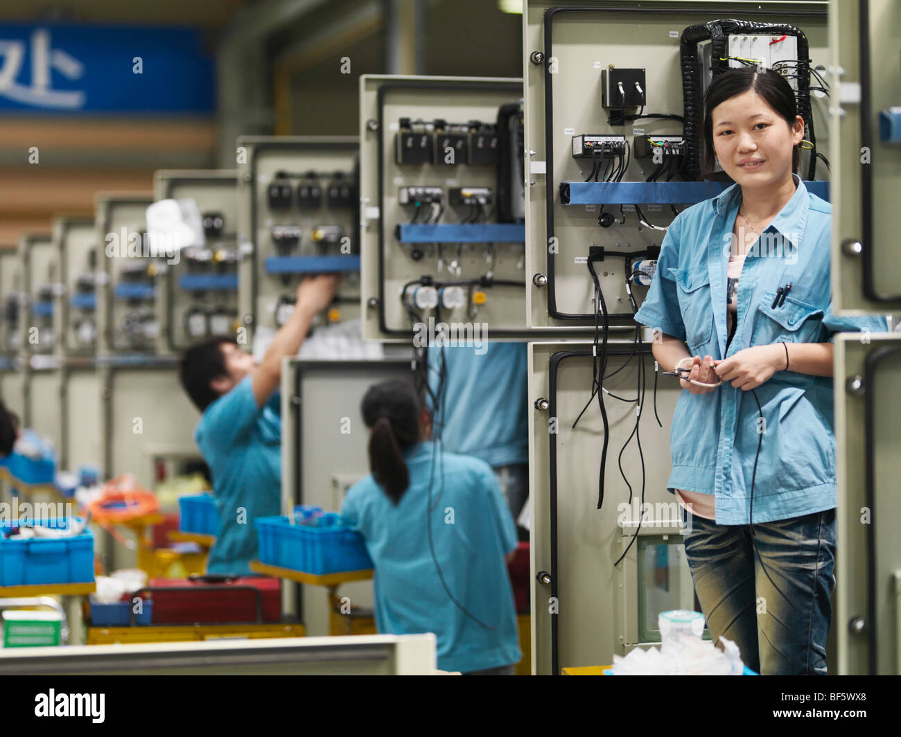 A factory worker standing at her work station in the assembly line. - Stock Image
