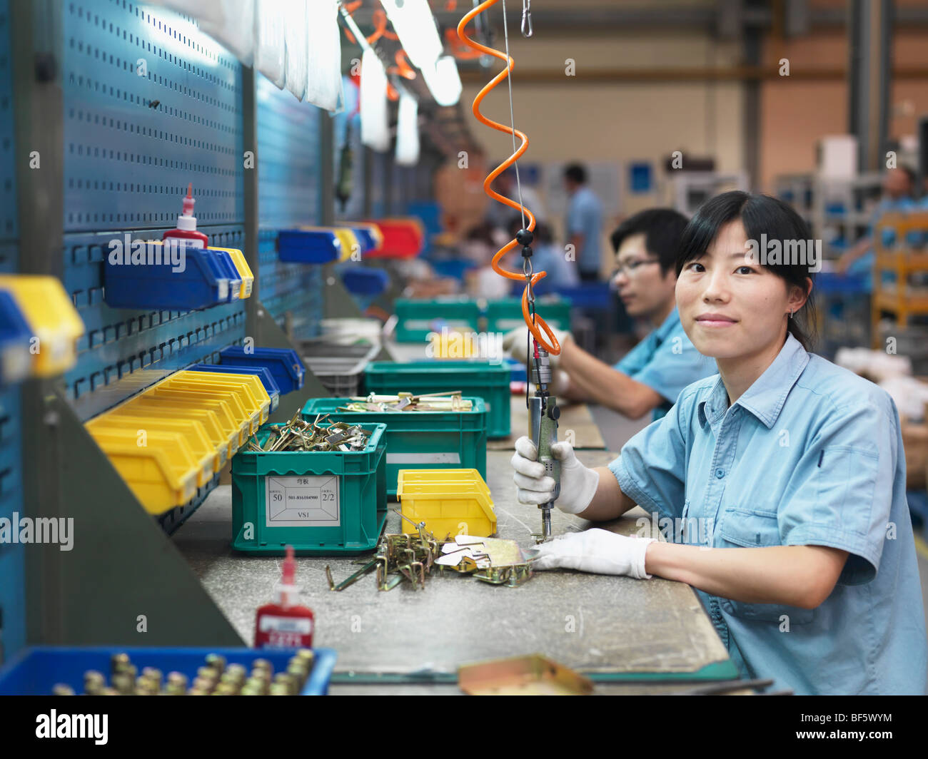 A woman bolting parts of hardware together in a factory assembly line. Stock Photo