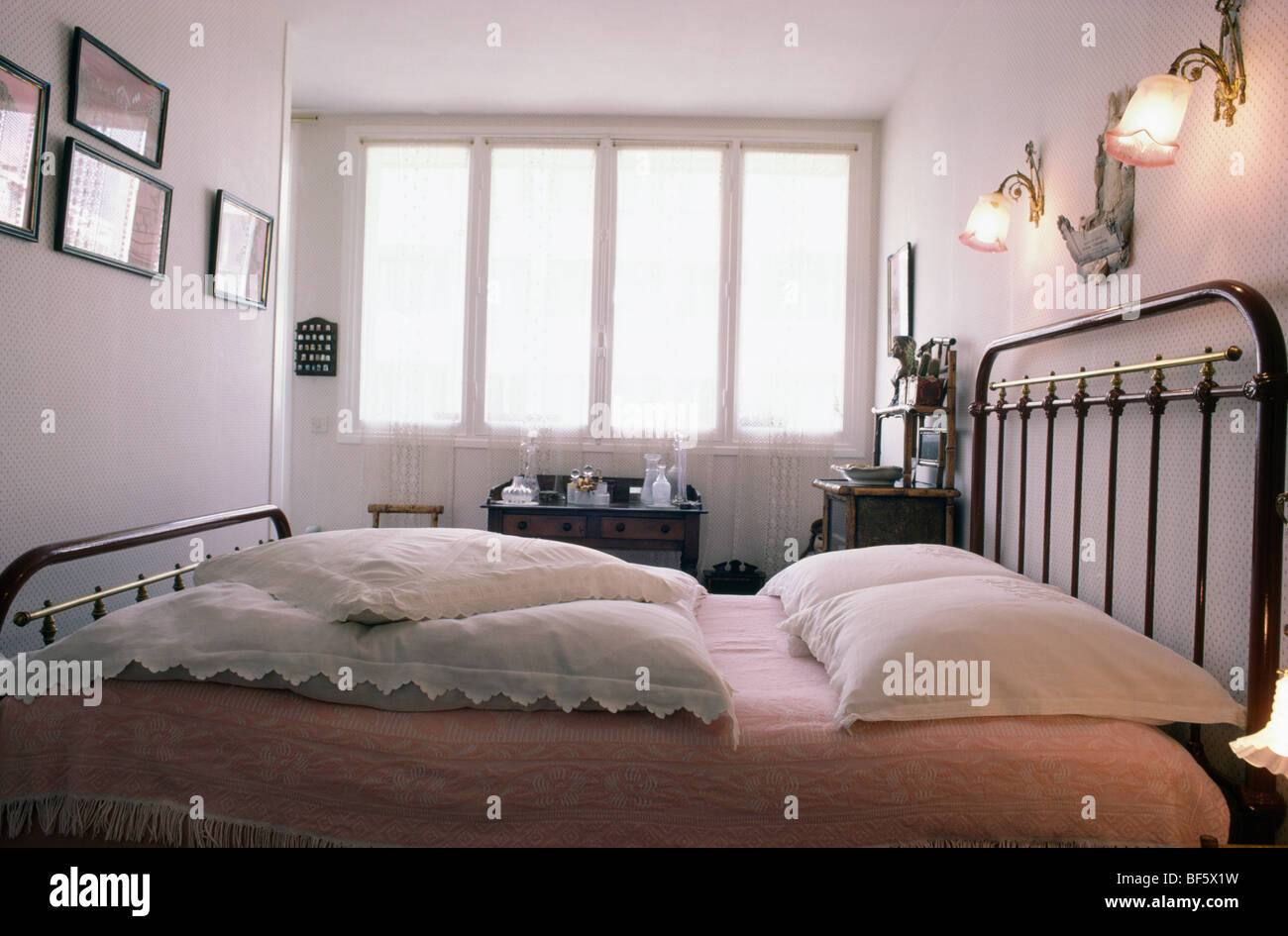 lights above bed victorian glass walllights above black metal bed with white lace pillows in small bedroom