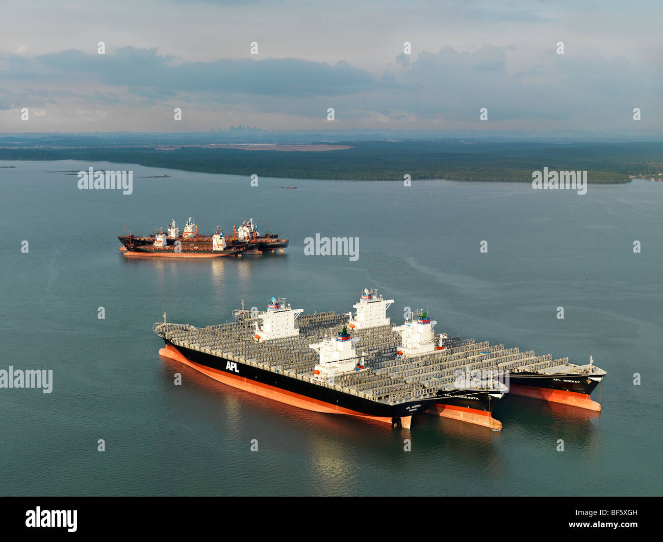 Freight ships anchored next to each in order to hold the large sections of a suspension bridge under construction. - Stock Image