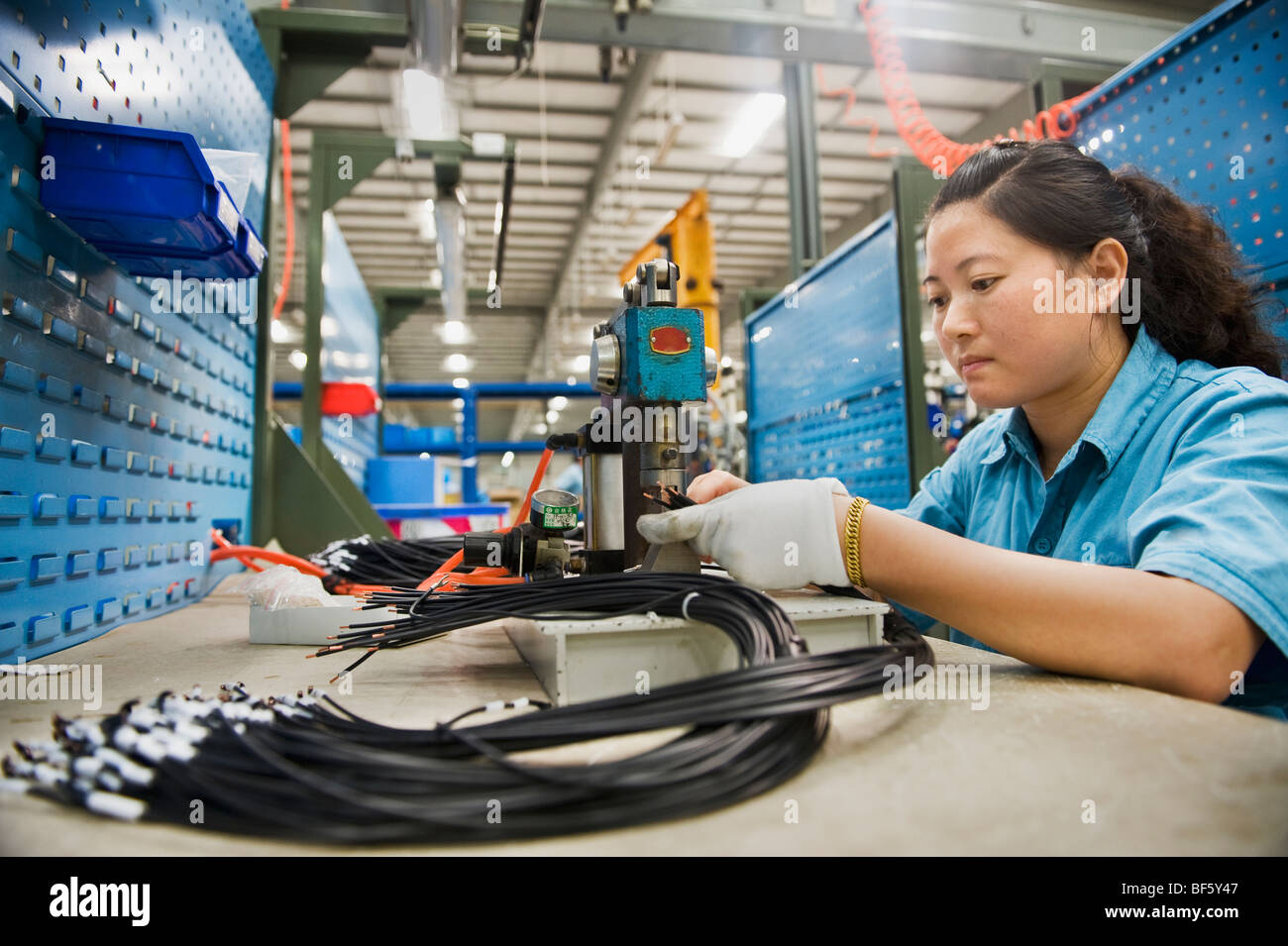 A  factory employee clamping and sodding small parts. - Stock Image