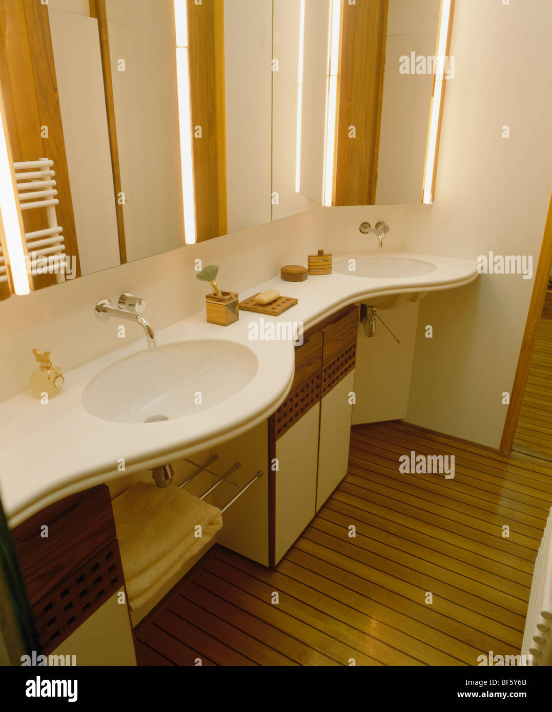 Strip lighting on mirror above basin in curved cream vanity unit ...