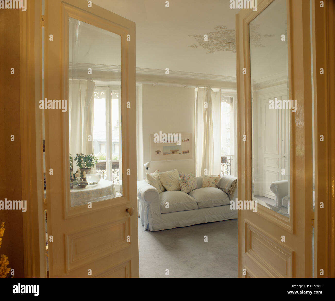 Half Glazed Double Doors Open To Traditional Apartment Living Room With  White Sofa And Tall Ceilings