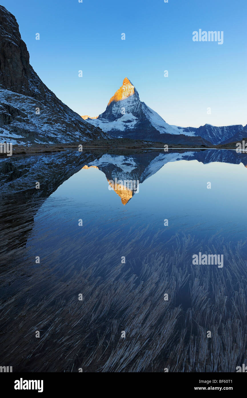 Matterhorn at sunrise in winter with reflection in the Riffelsee, Zermatt, Valais, Switzerland, Europe - Stock Image