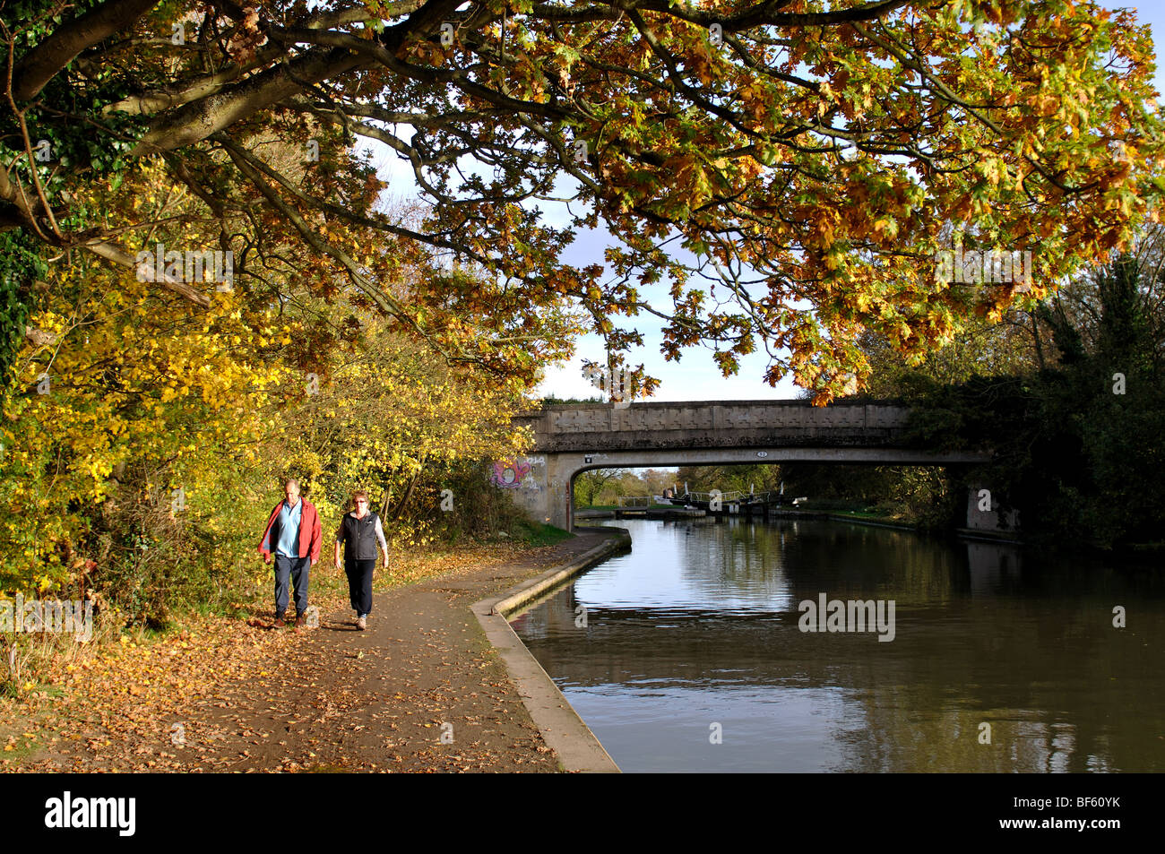 Couple walking along canal towpath in autumn, Hatton Locks, Grand Union Canal, Warwickshire, England, UK - Stock Image