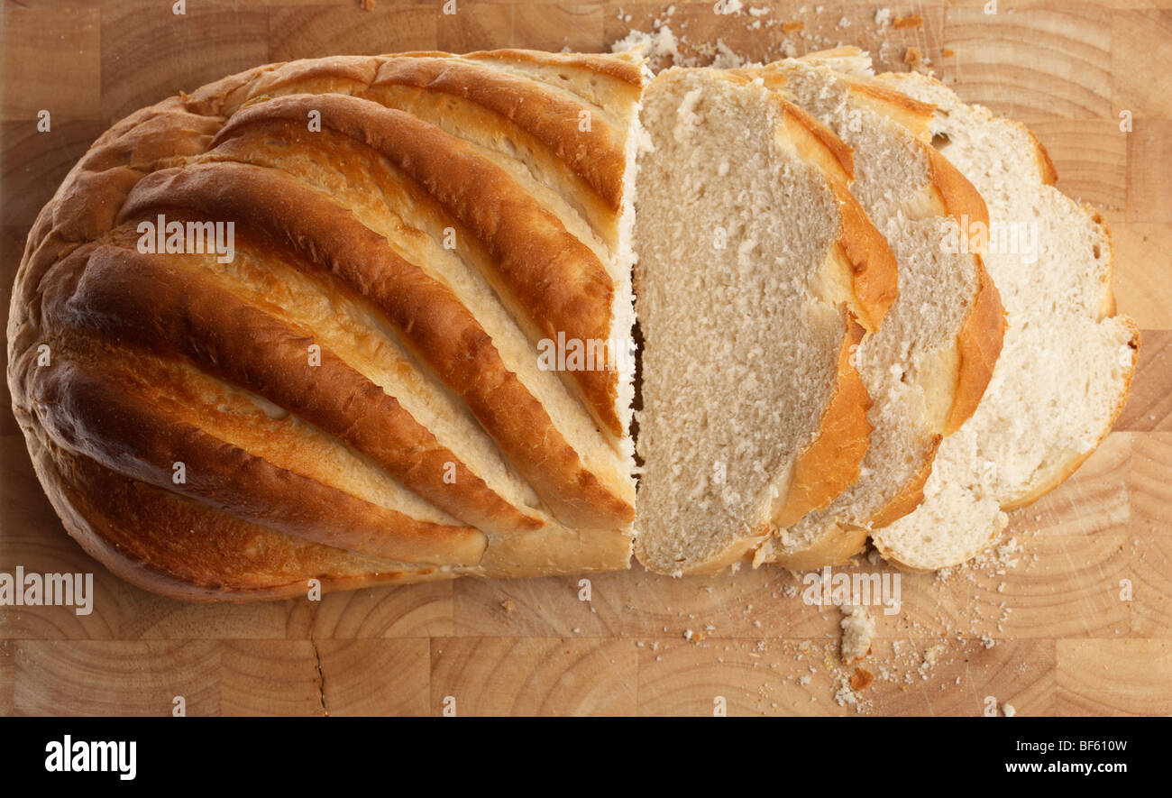 fresh white crusty bloomer loaf cut into rough slices on a wooden block - Stock Image