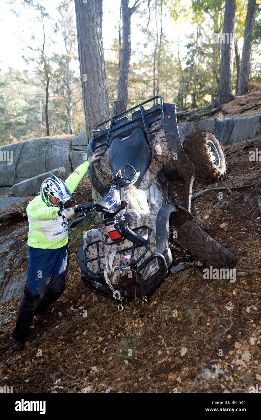 Man struggles to maintain control over his all-terrain vehicle on very steep terrain. - Stock Image