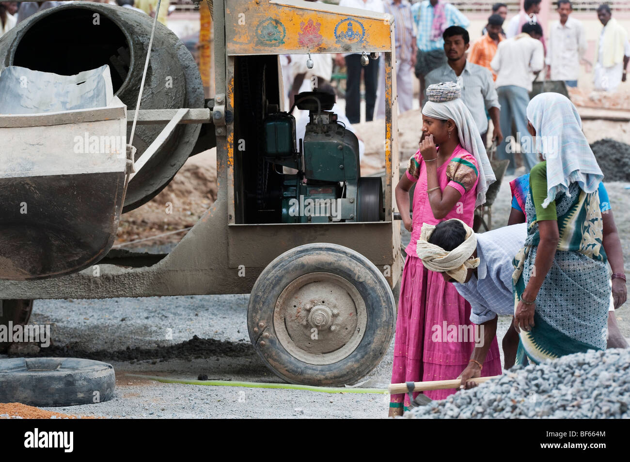 indian women standing next to a large concrete mixer whilst working on the roads in Puttaparthi, Andhra Pradesh, - Stock Image