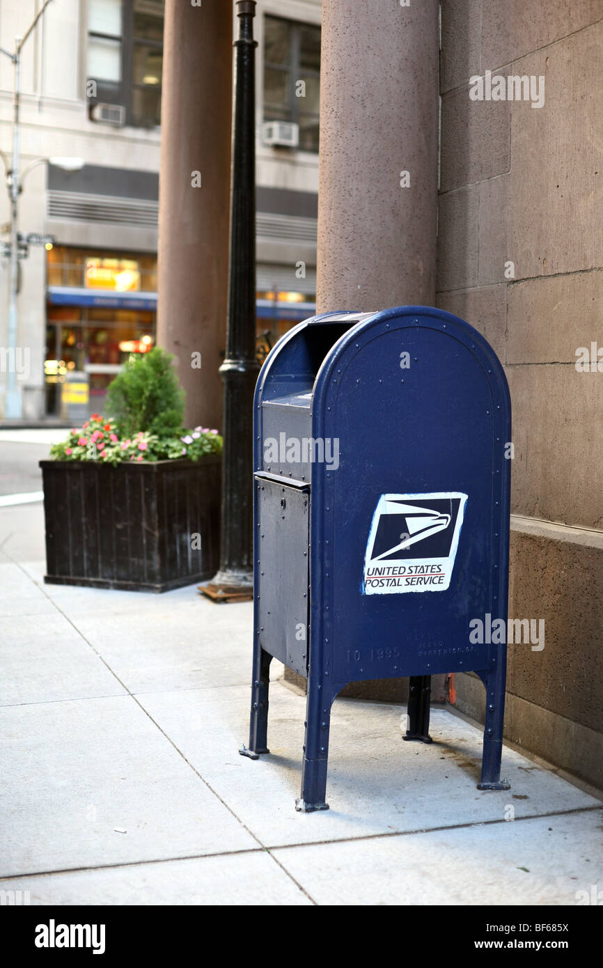 appealingly homely bright blue United States Postal Service mail box & logo on a lower Manhattan street corner - Stock Image