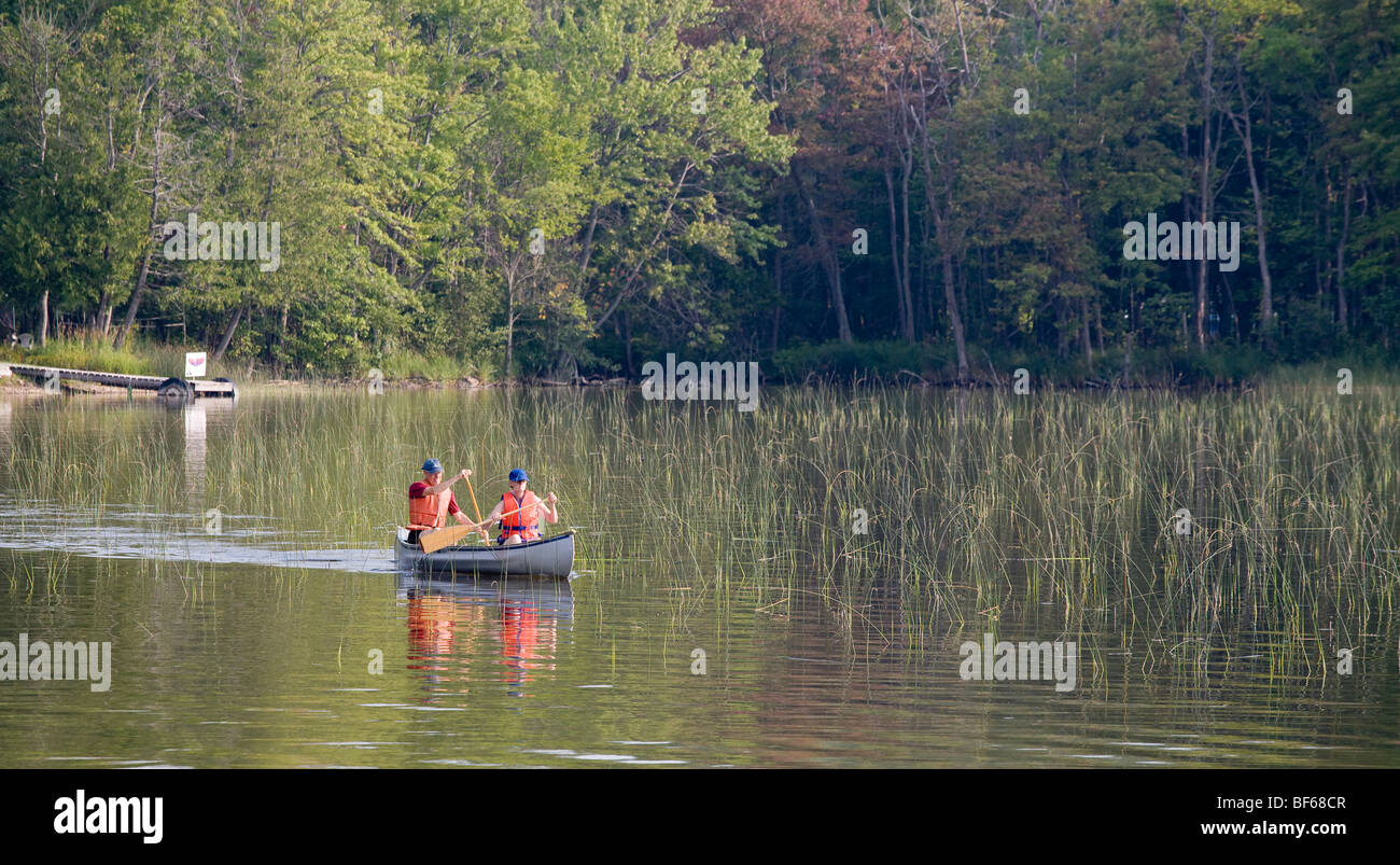 Morning Canoe Paddle. A couple, both wearing life vests, enjoys a morning paddle on a smooth but weedy small Quebec - Stock Image